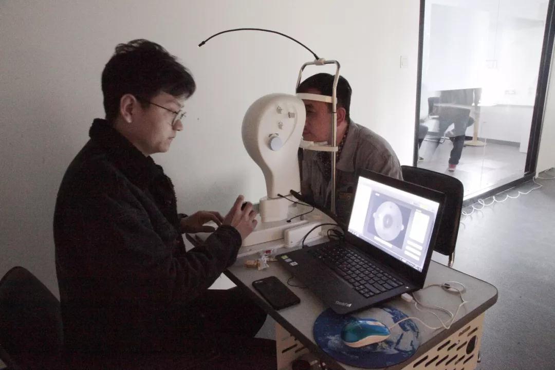 工作人員為員工進行視力測試、屈光數據采集及拍攝眼底照片
