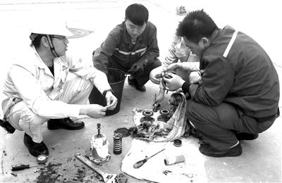 图为该车间技术人员正在修复阀门